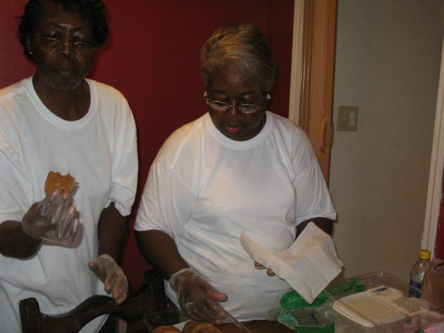 two ladies preparing plates of food in a line