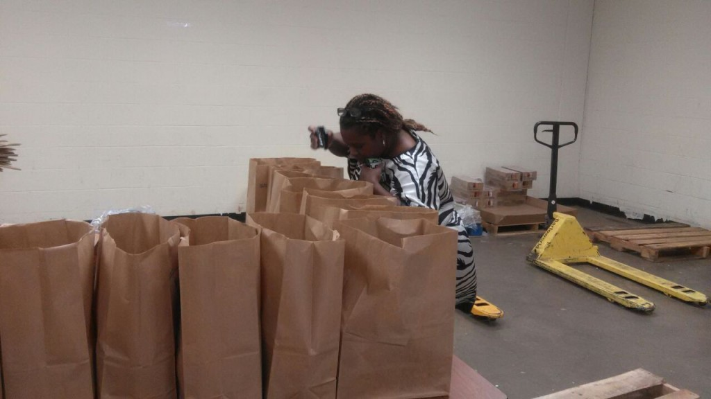 Minister Fern putting food items in a bag
